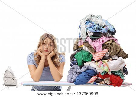 Sad woman posing next to a pile of clothes for ironing isolated on white background