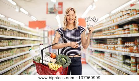 Woman shopping in a supermarket and holding a few stacks of money