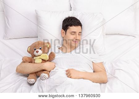 Joyful childish guy sleeping peacefully with a teddy bear on a comfortable bed