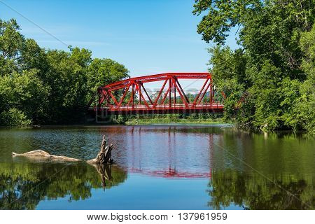 Red Bridge in bright daylight on Route 32 over the Wallkill River near Rifton in the Catskills of Upstate New York. Selective focus on the bridge. Selective focus on bridge.