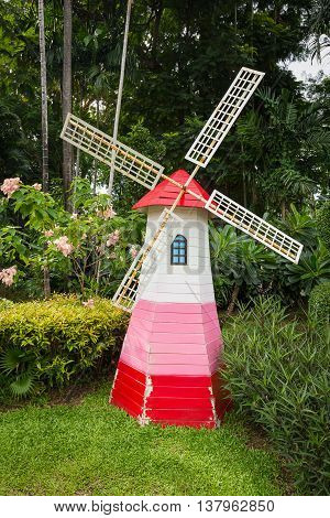 Colorful lighthouse wind turbine decorating in green garden surround by flowers bush and tree