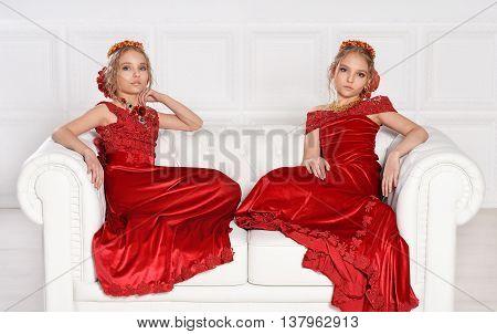 portrait of beautiful  little girls in red dresses  in studio