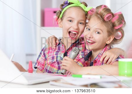 Cute  tweenie girls  in hair curlers  with laptop and  microphone  at home poster