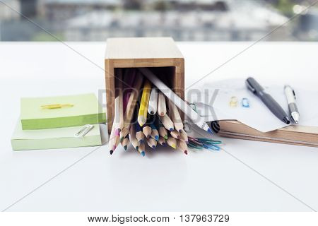 Closeup of white desktop with colorful pencils in fallen wooden holder green stickers pens and closed notepad on blurry city background