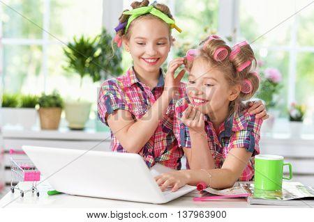 Cute  tweenie girls  in hair curlers  with laptop at home