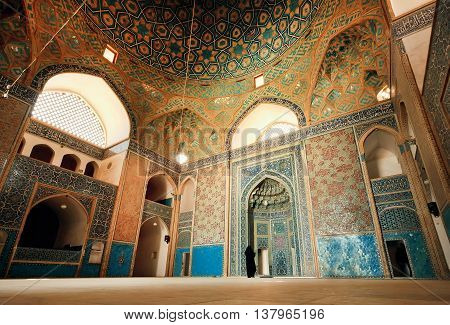 YAZD, IRAN - OCT 19, 2014: Wide colorful hall of ancient mosque and lonely woman praying inside on October 19, 2014. With population of 270.600 families Yazd is centre of Persian architecture