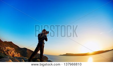 panoramic view on Balos beach, Crete, Greece. Man, traveller and photographer stands on the cliff and taking photo