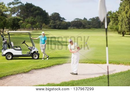 Male golfer playing on sand trap by woman standing at golf course