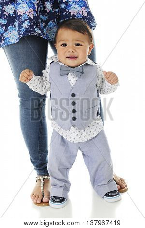 An adorable, dressed-up baby boy looking mighty worried as he stands without hanging on.  His mother's legs and feet are securely behind him giving him some support.  On a white background.