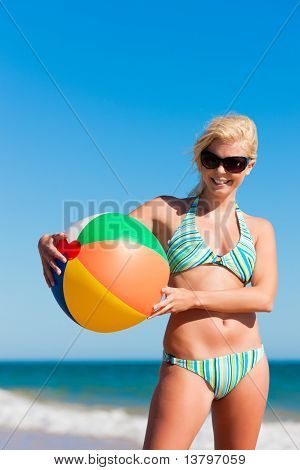 Attractive Woman in bikini standing in the sun on beach under a blue sky � she is looking into the sky