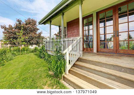 Backyard Of Big Farmhouse With Beautiful Flowerbed