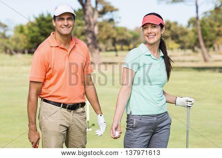 Portrait of smart golfer couple standing on field