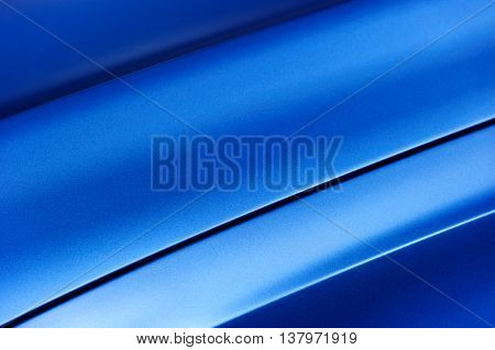 Surface of blue sport sedan car metal hood, part of vehicle bodywork, steel gradient line pattern