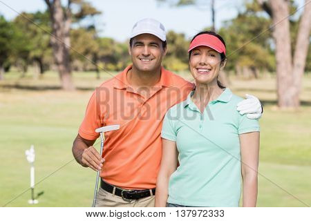 Portrait of smiling golfer couple with arm around while standing on field