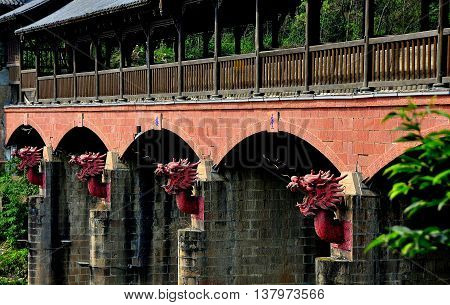 Jie Zi Ancient Town, China - March 6 2013: The Dragon covered bridge decorated with four terra cotta dragon heads on each of its stone support bastions