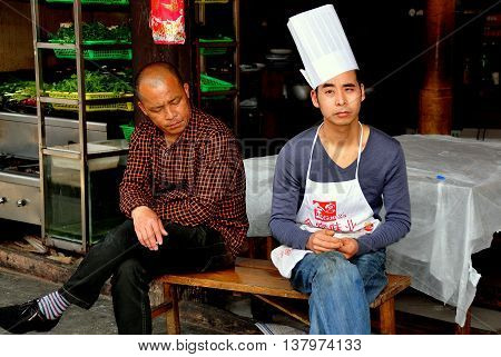 Jie Zi Ancient Town China- March 6 2013: Chef in toque hat and co-worker sitting in front of a restaurant on Jinyu Street