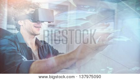 Fish swimming with shark in darkest water against businessman wearing virtual glasses
