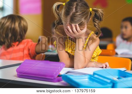 Frustrated girl with hand covering face in classroom