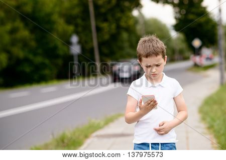 Child Playing Mobile Games On Smartphone On The Street