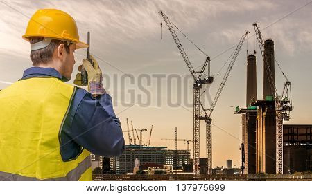 Worker Is Using Radio And Crane Site. Construction Concept.