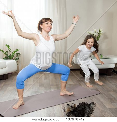 Pregnant Mother Doing Fun Yoga Training With Her Kid Girl And Pet Playing Around At Home
