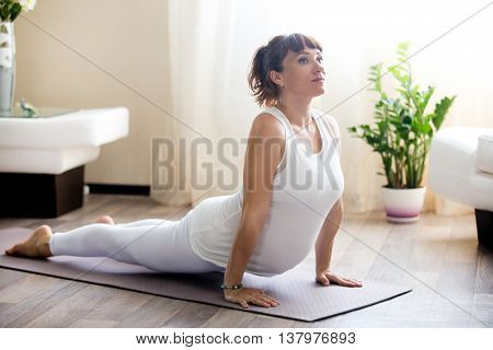 Pregnant Woman Doing Upward Facing Dog Yoga Pose At Home