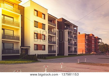 New multi-family block with balconies and bright facade decorated with wood paneling.