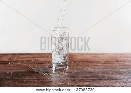 Pouring water into glass on wooden table