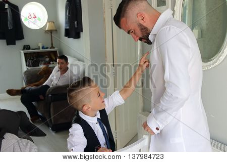 2ND JULY 2016, PORTSMOUTH,ENGLAND:A young boy being watched as he is dressing his father on his wedding day as part of his best man duties, portsmouth, england,2nd july 2016