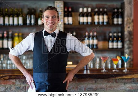 Portrait of confident waiter standing in front of bar counter