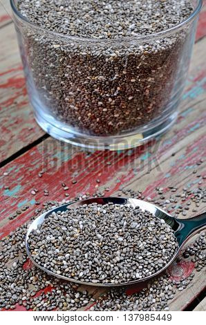 Metallic spoon with chia seeds on wooden background