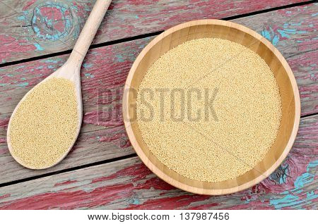 Bowl with amaranth seeds on wooden table