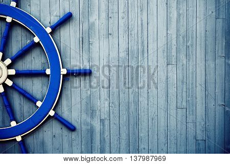 Old Vintage Blue Wooden Helm Wheel on the wall