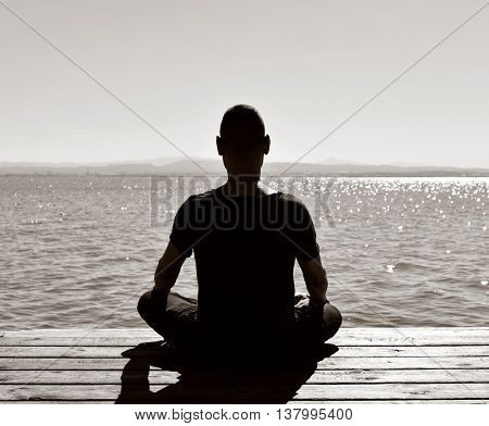 young man seen from behind meditating in the lotus position in an old wooden pier over the sea or over a lake, in black and white