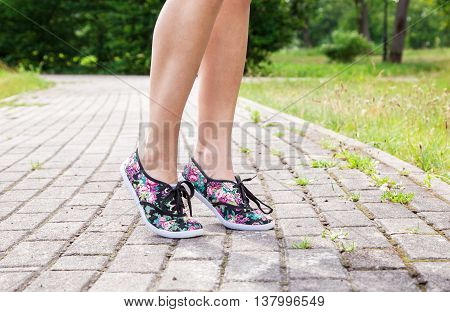 legs of a woman walking on the sidewalk in the park on sunny summer day closeup