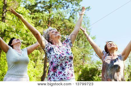 Portrét tří starých žen s rukama zvedl a užijte si