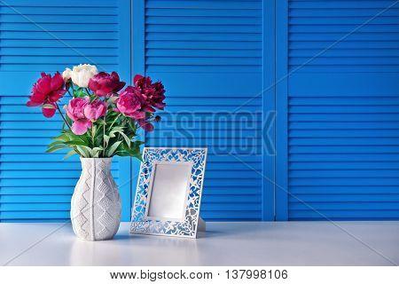 Beautiful peony bouquet on blue folding screen background