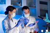 science, chemistry, biology, medicine and people concept - close up of young scientists with pipette and flasks making test or research in clinical laboratory poster
