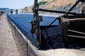industrial pavement truck laying fresh asphalt on construction site poster