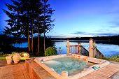Awesome water view with hot tub at dusk in summer evening. House exterior. poster