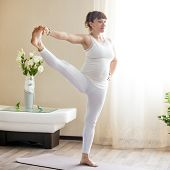 Healthy Pregnancy Yoga and Fitness concept. Young smiling pregnant yoga woman working out at home. Pregnant happy model doing prenatal Utthita Hasta Padangustasana Extended Hand to Big Toe yoga pose poster