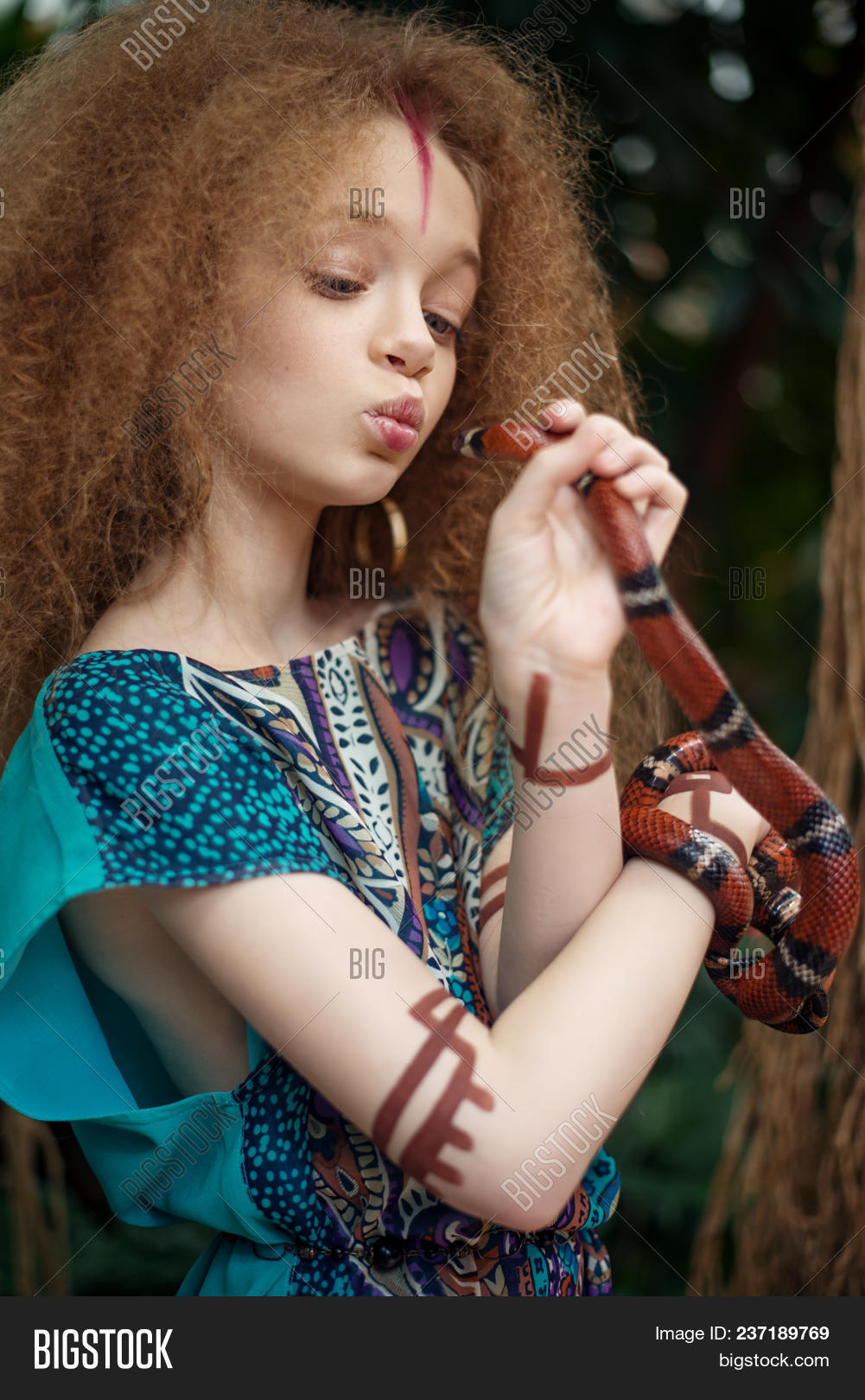 A Beautiful Little Girl With Snake Wearing Native Costume In The Jungle Or Rainforest.