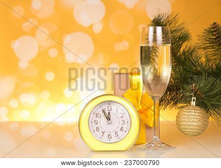 Christmas Pine Branch With Toy, Glass Of Champagne, Gift And Clock On Bright Yellow Background