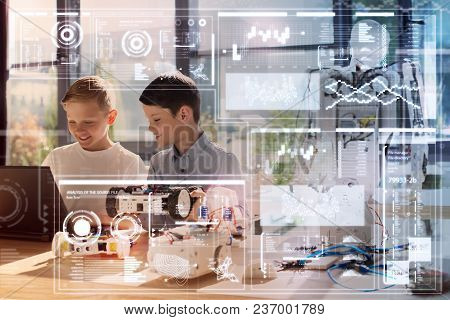 Productive Morning. Cheerful Attentive Clever Boys Standing In Front Of A Modern Laptop And Looking