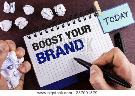 Text sign showing Boost Your Brand. Conceptual photo improve your models name in your field overcome competitors written by Man Notepad holding Marker wooden background Crumpled Paper Balls poster