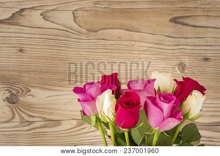 A Bouquet Of Roses In Front Of A Wood Background