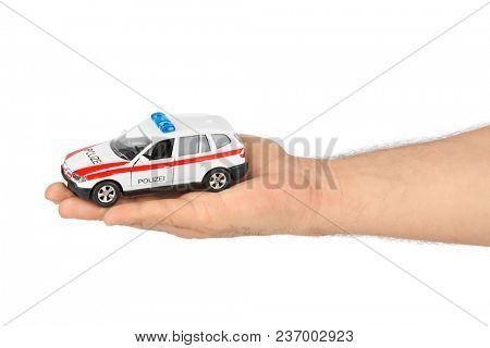 Hand with toy police car isolated on white background