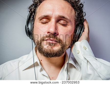 enjoy the music, man with intense expression, white shirt
