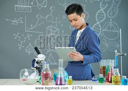 Portrait Shot Of Handsome Asian Student Sitting On Edge Of Desk And Using Modern Digital Tablet Whil