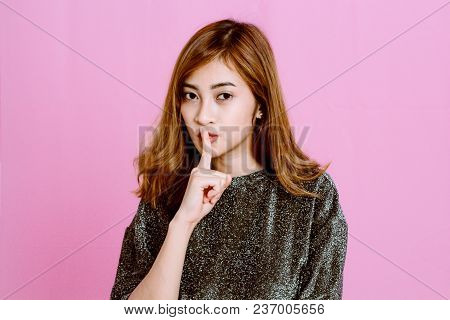 Woman Quiet Gesture With Finger On Pink Background